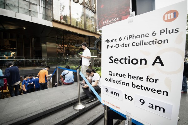 Apple fans queue up outside an M1 store in Singapore for the new iPhone.